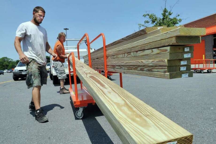 """Billy Bradt of Bradt Construction, of Coxsackie, left, and Lowell Radley of Radley Construction , of Stephentown,  right, load lumber onto a truck for a residential job they're working on together , at a Home Depot on Tuesday July 5, 2011 in Albany, NY.  """"Its picked up a lot this year,"""" said Bradt of their work, with Radley in agreement.   ( Philip Kamrass /  Times Union) Photo: Philip Kamrass"""