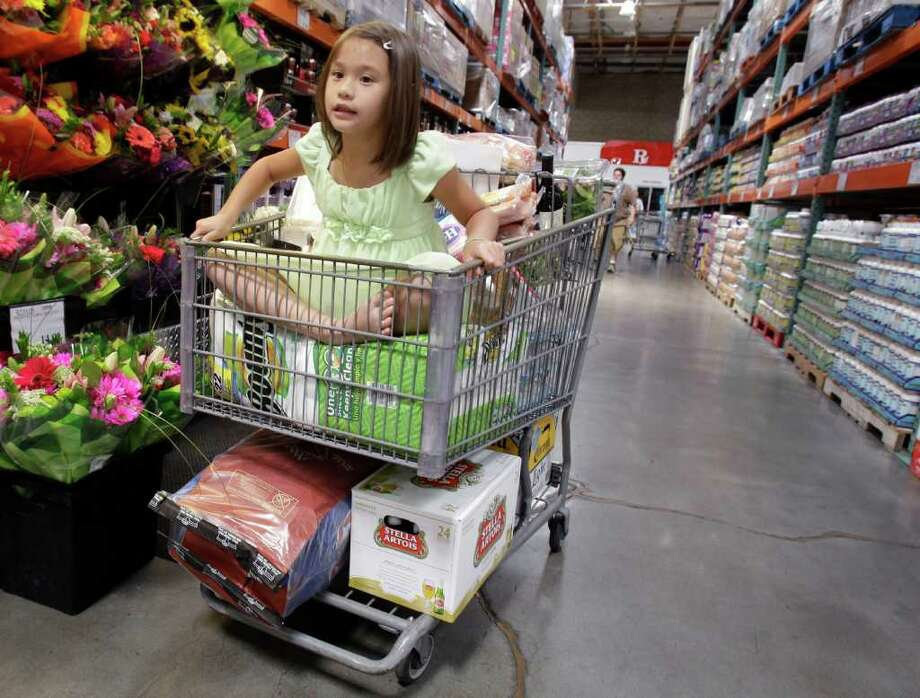 In this June 17, 2011 photo, a girl sits in a shopping cart full of items at Costco in Mountain View, Calif. Shoppers go into Costco, TJ Maxx or a DSW shoe store looking for a bargain on something they need and end up splurging on irresistible finds.(AP Photo/Paul Sakuma) Photo: Paul Sakuma