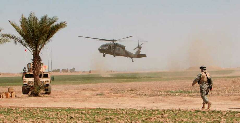 FILE - In this March 17, 2006 file photo, a U.S. helicopter lands in the field as a U.S. soldier stands guard outside Samarra, Iraq. The White House is planning to keep up to 10,000 troops in Iraq next year, despite opposition not only from Iraqis but also key Democratic Party allies who demand that President Barack Obama bring home the U.S. military as he promised as a candidate. (AP Photo/Khalid Mohammed, File) Photo: Khalid Mohammed / AP