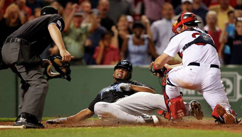 Toronto Blue Jays' Edwin Encarnacion, center, slides into home plate as Boston Red Sox catcher Jason Varitek, right, prepares to tag him out  in the ninth inning of a baseball game at Fenway Park, in Boston, Tuesday, July 5, 2011.  The Red Sox defeated the Blue Jays 3-2. Home plate umpire Brian Knight looks on at left. (AP Photo/Steven Senne) Photo: Steven Senne