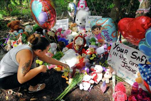 "Tiffany Miller, of Sanford, Fla., leaves stuffed animals and candle at a makeshift memorial on Suburban Drive where the remains of Caylee Anthony  was found in Orlando, Fla., Tuesday afternoon, July 5, 2011. In one of the most divisive verdicts since O.J. Simpson was acquitted in 1995 of murdering his wife, Anthony was cleared Tuesday of murder, manslaughter and child-abuse charges after weeks of wall-to-wall TV coverage and armchair-lawyer punditry that one of her attorneys denounced as ""media assassination."" (AP Photo/Florida Today, Craig Rubadoux)  NO SALES Photo: AP"
