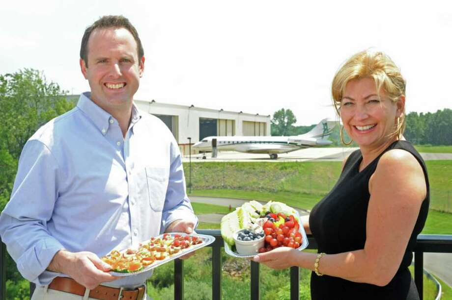 General manager John Hetzel and owner Michele Savino, of In Flight Catering, stand on the deck at 121 Restaurant at Waterbury-Oxford Airport with some of their selections. Photo: Autumn Driscoll / Connecticut Post