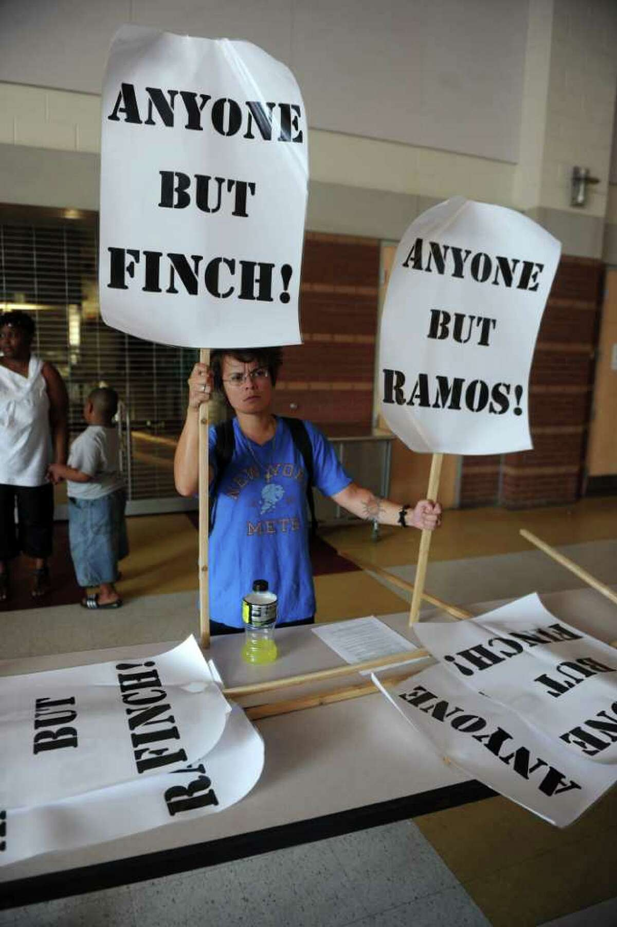 Cat Vendryes-Martin hold up signs protesting the Mayor Bill Finch and Superintendant of School Dr. John Ramos during a special meeting of the Bridgeport Board of Education was held at Cesar A. Batalla Elementary School in Bridgeport, Conn. on Tuesday July 5, 2011.