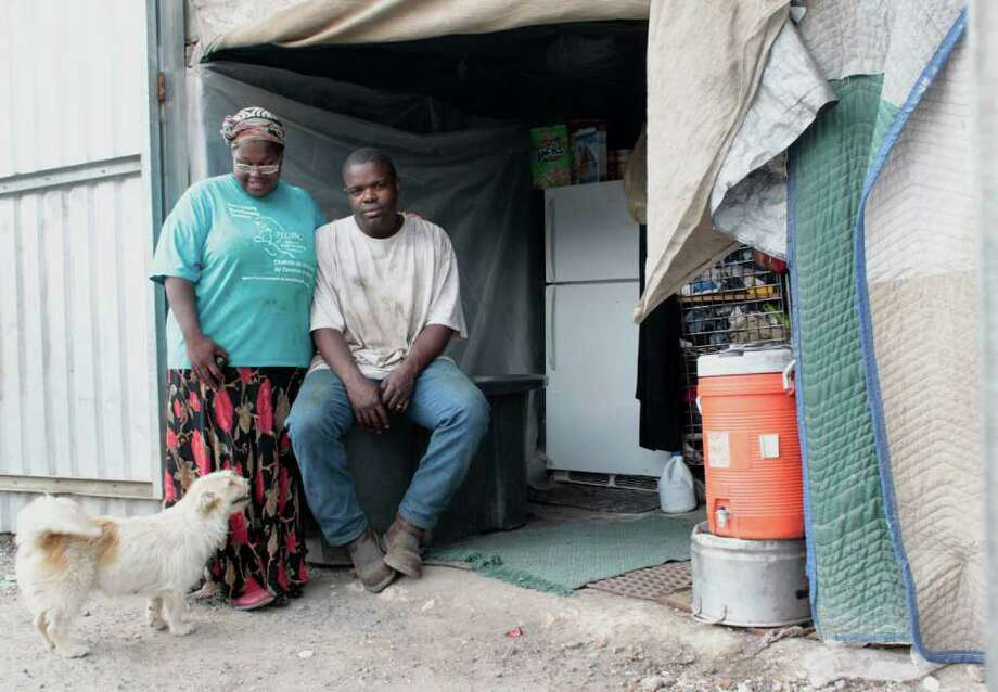 (l-r) Charlomane Leonard stands next to her husband Prince Leonard in front of the entrance to there shelter, Wednesday July 7, 2011.  For four-years The Leonards had been using a storage unit at Boat & RV stoarge in the 12000 block of  McNair  Houston, TX as the shelter for them and their six children. Three weeks ago Child Protective Services took their children because the storage facility was unfit for children. (Billy Smith II/ Houston Chronicle) Photo: Billy Smith II / 2011 Chronicle
