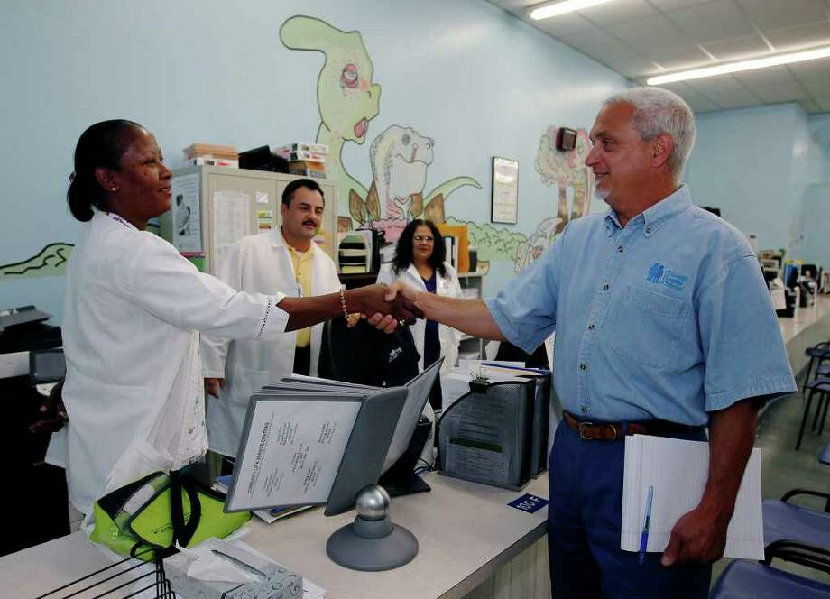 Dr. Thomas Schlenker (right) shakes hands with Pam Long during a meeting with staff at the Metro Health immunization clinic. He was hired as Metro Health director in May. Photo: Kin Man Hui/kmhui@express-news.net / San Antonio Express-News