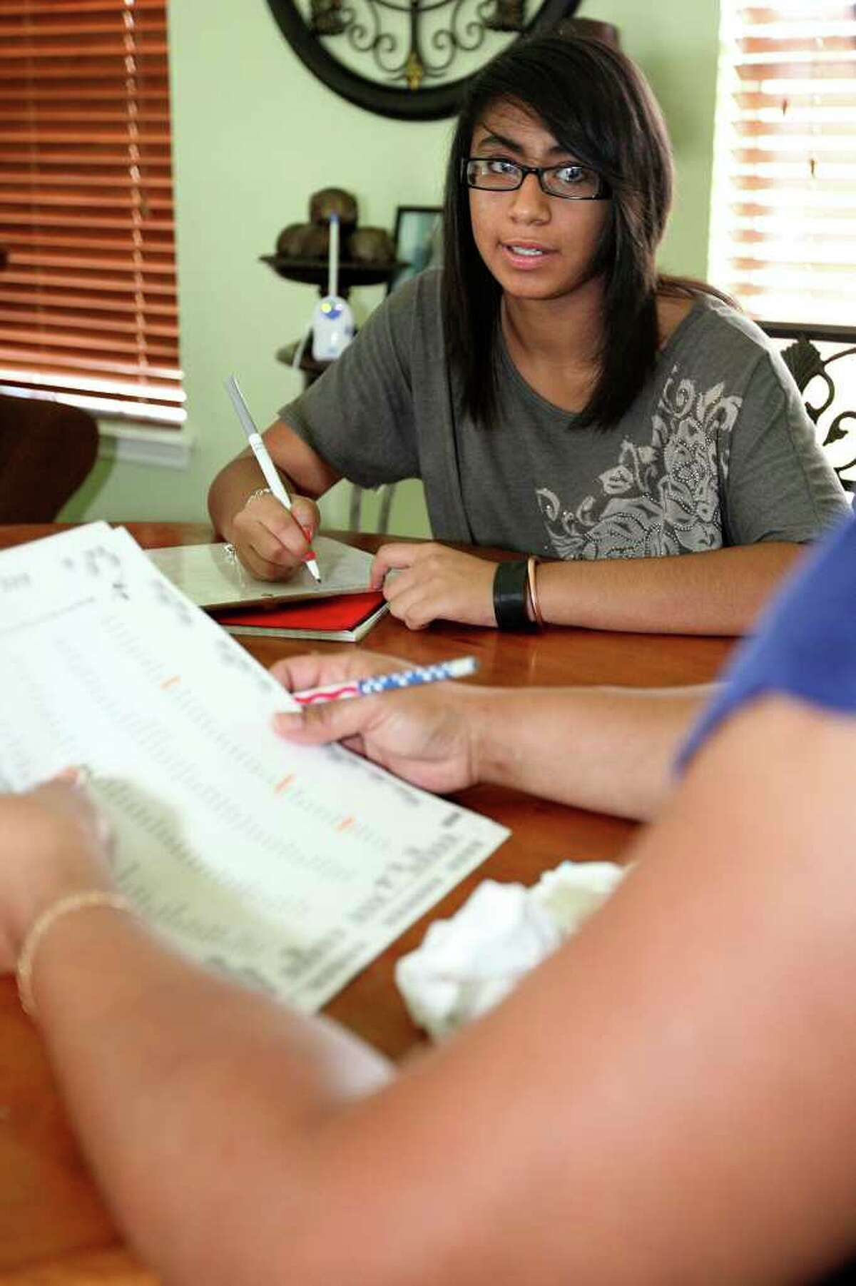 Linda Duann Rodriguez studies a spelling bee word list with her mother.