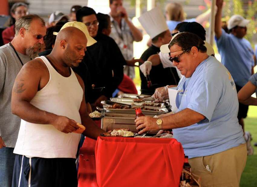 Greg Kaneb (right) serves barbecue to Sean Wharton during a one-year anniversary celebration for Haven for Hope on Wednesday, July 6, 2011, at the downtown campus for the homeless. NuStar Energy sponsored the barbecue.