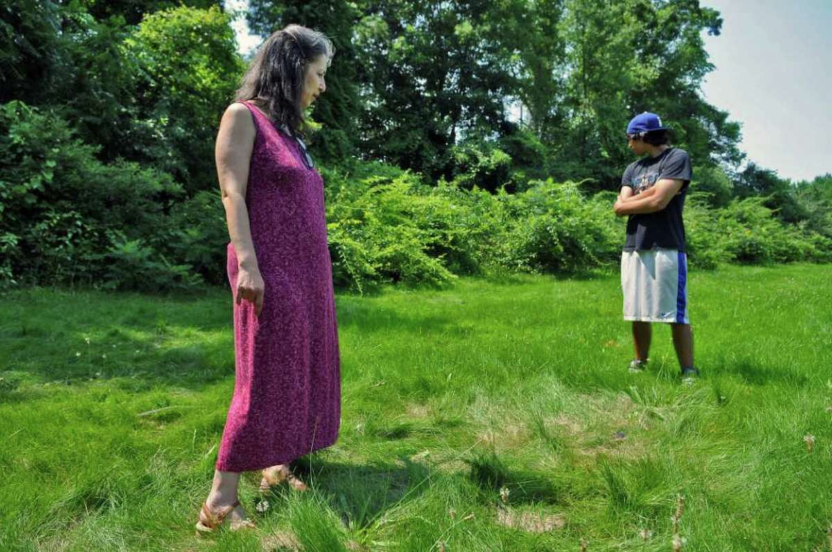 Joanna Sanchez and her son Antonio, 19, stand by flattened grass surrounding a small animal carcass, as they check for signs of a fox's presence in a wooded area near her backyard on Tuesday July 5, 2011 in Colonie, NY. ( Philip Kamrass / Times Union)