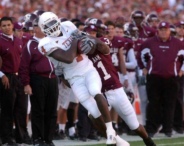 SPORTS - Texas receiver Roy Williams comes down with a catch as Texas A&M's Sean Weston defends during action in College Station on Friday, Nov. 28, 2003. BILLY CALZADA Photo: BILLY CALZADA, SAN ANTONIO EXPRESS-NEWS