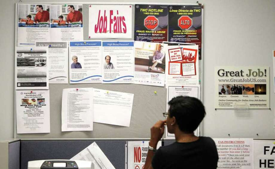 A job seeker looks at a bulletin at the Texas Workforce Commission's Workforce Solutions of Greater Dallas job resource center in Richardson, Texas Tuesday, July 5, 2011. The number of people applying for unemployment benefits fell last week to the lowest level in seven weeks, although applications remain elevated.  (AP Photo/LM Otero) Photo: LM Otero, STF / AP
