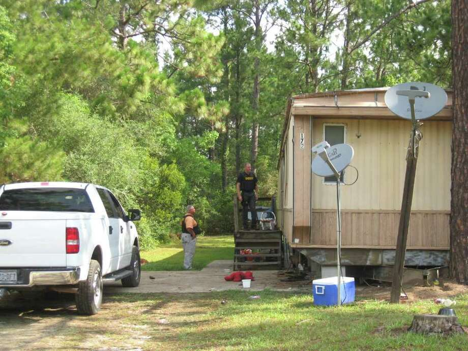 Chief Deputy Kenny Davenport and narcotics Sargeant Mark Vincent track down a suspect at his Kountze home Wednesday. The Hardin County Sheriff's Office arrested 11 people wanted on drug-related charges. Photo: Jessica Lipscomb