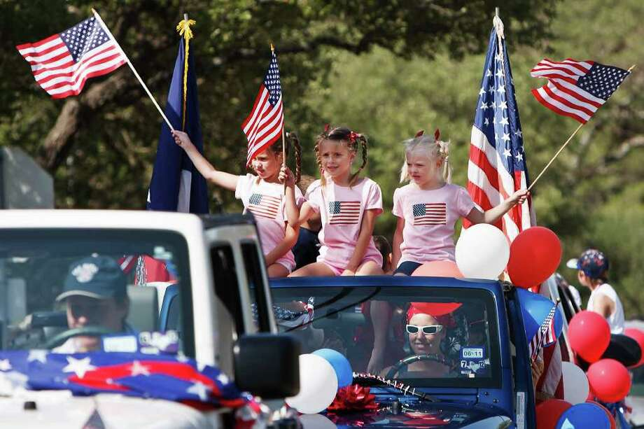 Samantha Daniel (from left), Alyssa Stewart and Katie Stewart wave American flags from atop their jeep during the Hollywood Park 4th of July Parade on July 4, 2011.  Photo by Marvin Pfeiffer Photo: MARVIN PFEIFFER, Marvin Pfeiffer/Prime Time Newspapers / Prime Time Newspapers 2011