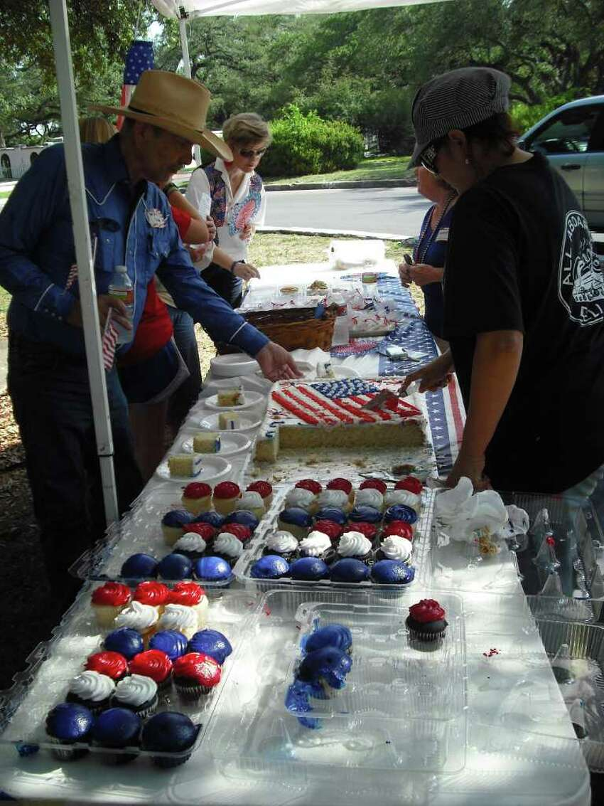 Olmos Park residents, including Mayor Susan Gragg (left background) browse patriotic treats at the city's Fourth of July picnic Monday at Alameda Circle. The food pictured here were offered by Frankie Boone of Converse-based FrankieB Bakery & Catering (right background) and Olmos Park-based Sylvia Toscano of All Aboard Deli and Bistro (right forefront).