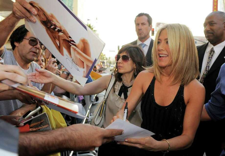 "Jennifer Aniston, a cast member in ""Horrible Bosses,"" signs autographs for fans at the premiere of the film, Thursday, June 30, 2011, in Los Angeles. The film is released on July 8. Photo: AP"