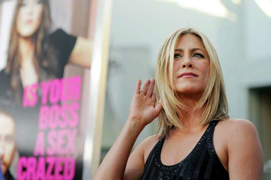 "Jennifer Aniston, a cast member in ""Horrible Bosses,"" strains to hear a photographer at the premiere of the film, Thursday, June 30, 2011, in Los Angeles. The film is released on July 8. Photo: AP"