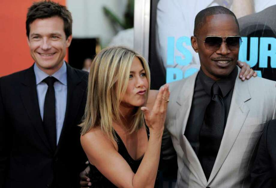 "Jennifer Aniston, center, a cast member in ""Horrible Bosses,"" blows a kiss as she poses with fellow cast members Jason Bateman, left, and Jamie Foxx at the premiere of the film, Thursday, June 30, 2011, in Los Angeles. The film is released on July 8. Photo: AP"