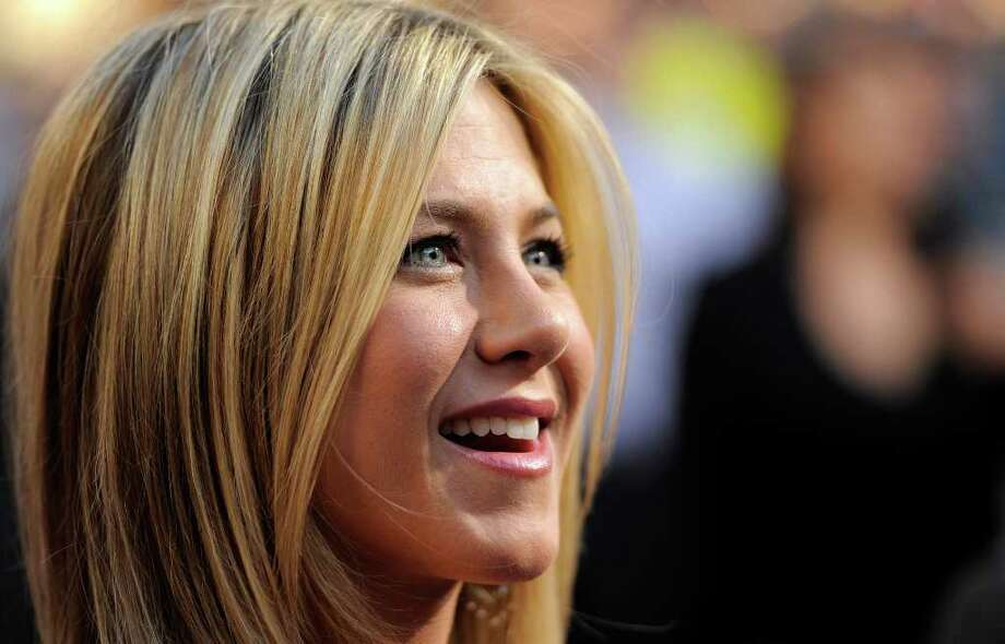 "Jennifer Aniston, a cast member in ""Horrible Bosses,"" reacts to photographers at the premiere of the film, Thursday, June 30, 2011, in Los Angeles. The film is released on July 8. Photo: AP"