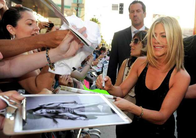 "Jennifer Aniston, right, a cast member in ""Horrible Bosses,"" signs autographs for fans outside the premiere of the film, Thursday, June 30, 2011, in Los Angeles. The film is released on July 8. Photo: AP"