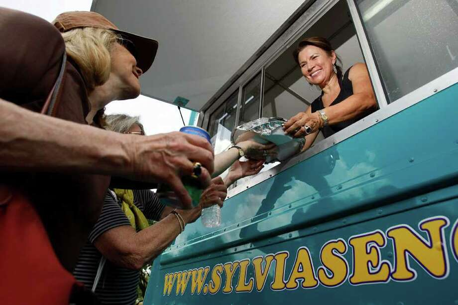 Sylvia Casares serves food to Francis Hill Barlow of New York City (left) at the No Borders food truck in a parking lot outside The Menil Collection before ordering food Friday, July 1, 2011, in Houston.  Known for being co-owners of Sylvia's Enchilada Kitchen, Sylvia Casares and Michael Warren have taken their kitchen on the road in a food truck serving tortilla's that are rolled out and cooked and tacos and enchiladas are served fresh. Photo: Johnny Hanson, Staff / © 2011 Houston Chronicle