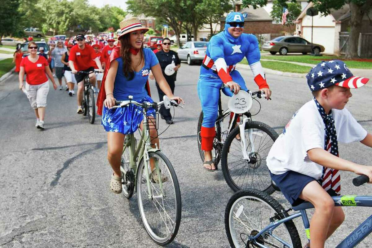 Captain America (Danny Silva) and Wonder Woman (Laura Silva) ride their bikes with the rest of the crowd as the Woodridge Indepence Day celebration makes it way up Woodrige Bluff on July 2, 2011. Photo by Marvin Pfeiffer