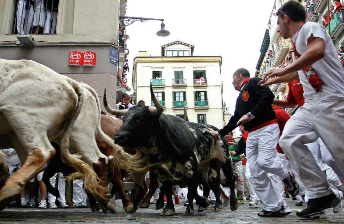 PAMPLONA, SPAIN - JULY 07: Runners and fighting bulls take a corner during the second day of the San Fermin running-of-the-bulls on July 7, 2011 in Pamplona, Spain. Pamplona's famous Fiesta de San Fermin, which involves the running of the bulls through the historic heart of Pamplona for eight days starting July 7th, was made famous by the 1926 novel of U.S. writer Ernest Hemmingway called 'The Sun Also Rises'. on July 7, 2011 in Pamplona, Spain. (Photo by Denis Doyle/Getty Images)