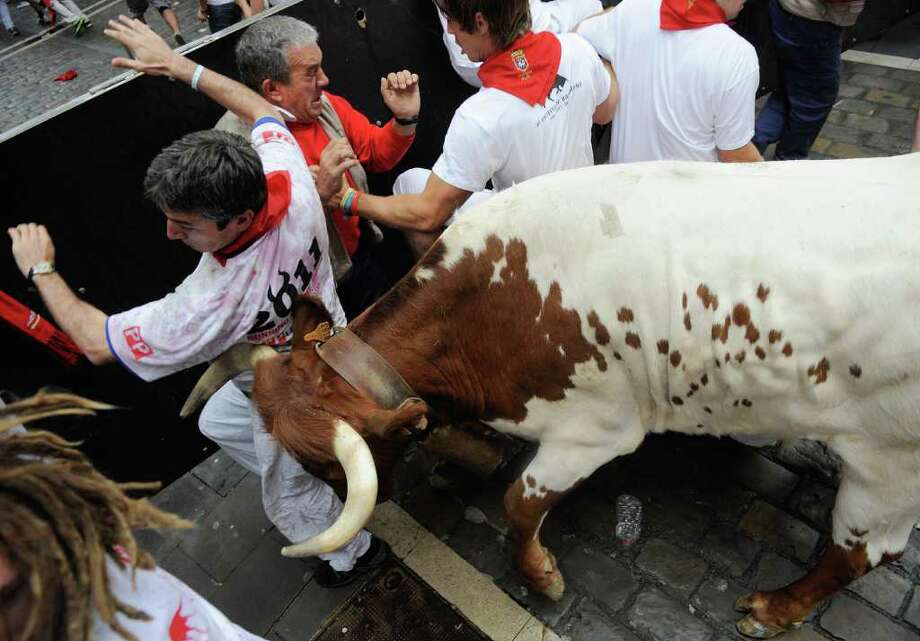 PAMPLONA, SPAIN - JULY 07:  A man tries to avoid a steer that broke away from the pact of fighting bulls during the second day of the San Fermin running-of-the-bulls on July 7, 2011 in Pamplona, Spain. Pamplona's famous Fiesta de San Fermin, which involves the running of the bulls through the historic heart of Pamplona for eight days starting July 7th, was made famous by the 1926 novel of U.S. writer Ernest Hemmingway called 'The Sun Also Rises'. on July 7, 2011 in Pamplona, Spain.  (Photo by Denis Doyle/Getty Images) Photo: Denis Doyle, Getty Images / 2011 Getty Images