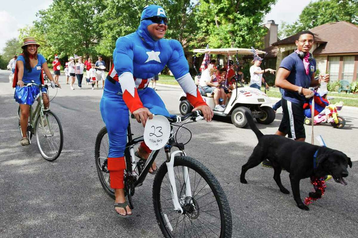 Captain America (Danny Silva) and Wonder Woman (Laura Silva) rode their bikes in the Woodridge Indepence Day celebration on July 2, 2011. Photo by Marvin Pfeiffer