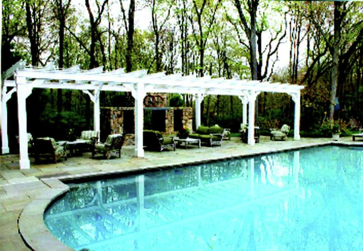 The swimming pool with a solar cover is highlighted by an Italianate pergola, stone fireplace and patios on the far side, and, of course, thereís a ceramic hot tub and a pool house.