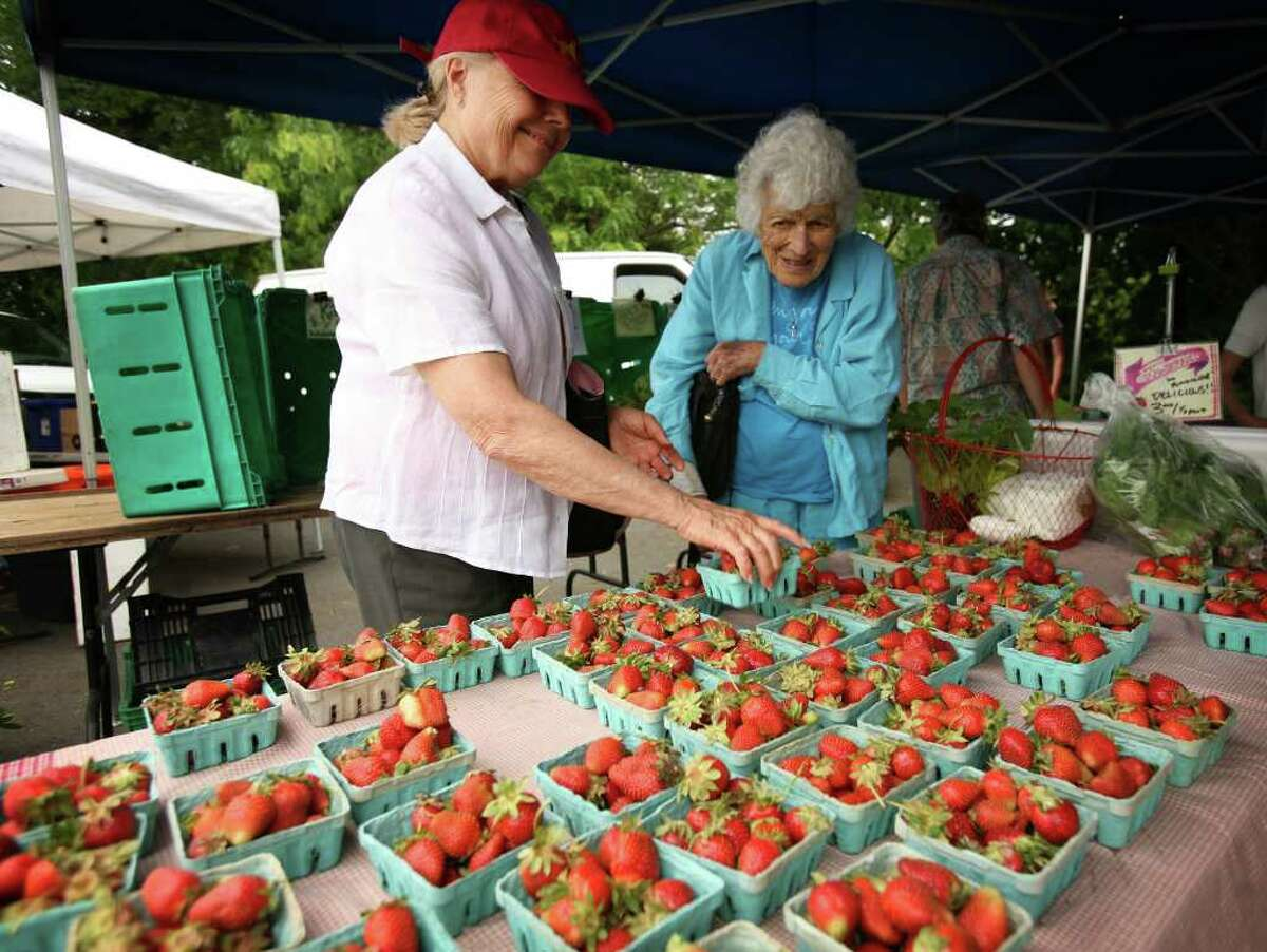 Shoppers look for fresh strawberries at the Westport Farmers' Market.