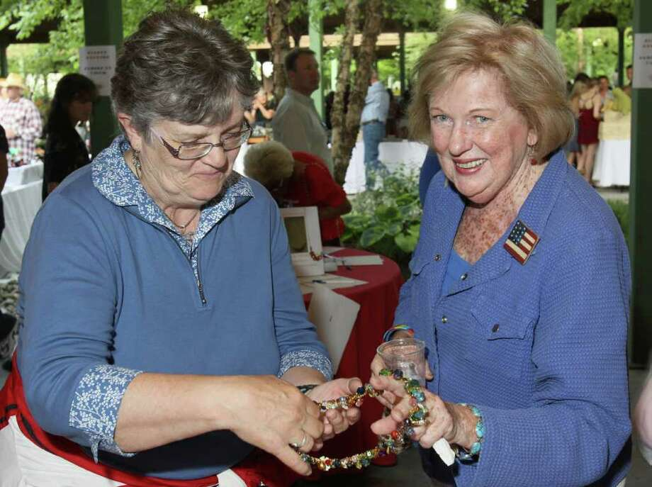 Lake George, NY - July 1, 2011 - (Photo by Joe Putrock/Special to the Times Union) - Event volunteer Sally Snowden(left) shows Judy Collins(right) a necklace from the silent auction table during the Double H Ranch 20th Anniversary Gala. Photo: Joe Putrock / Joe Putrock