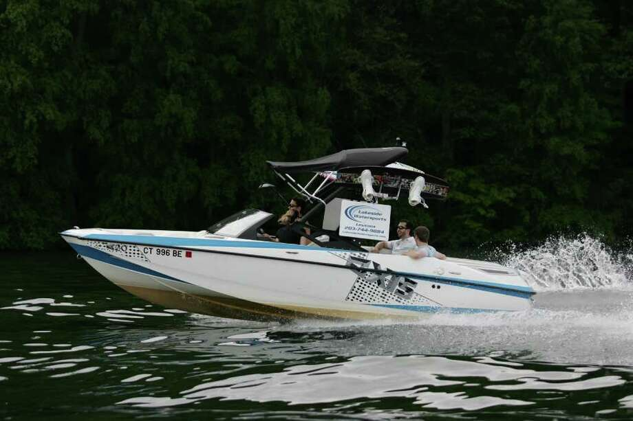 Chris Nuelle drives the boat for Lakeside Watersports while some customers enjoy the ride. Photo: Contributed Photo