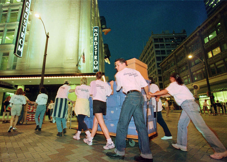 Nordstrom employees move a store full of merchandise into the new Nordstrom flagship store, across the intersection of Pine Street and Fifth Avenue in downtown Seattle Wednesday night, Aug. 19, 1998. Photo: Seattlepi.com File, Associated Press / AP