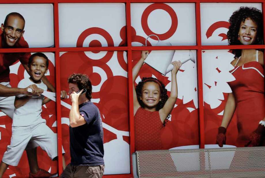 A man passes an advertisement for Target on the side of a store Wednesday, July 6, 2011, in San Diego. Retailers are reporting robust sales as deep discounts on summer merchandise pulled in shoppers in June. But the concern is that the momentum may not continue heading into the back-to-school shopping season when consumers are likely to find higher prices on everything from clothing to handbags.(AP Photo/Gregory Bull) Photo: Gregory Bull, STF / AP