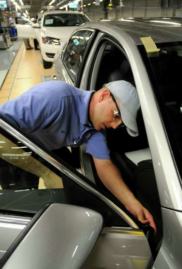 In this june 28, 2011 photo, Ben Edwards, team leader on assembly line number 6, works on the front door of a new Volkswagen Passat in Chattanooga, Tennessee. Mr. Edwards is a new auto employee at the Volkswagen plant which opened on May 24, 2011. (AP Photo/Billy Weeks) Photo: Billy Weeks, FRE / FR67639 AP