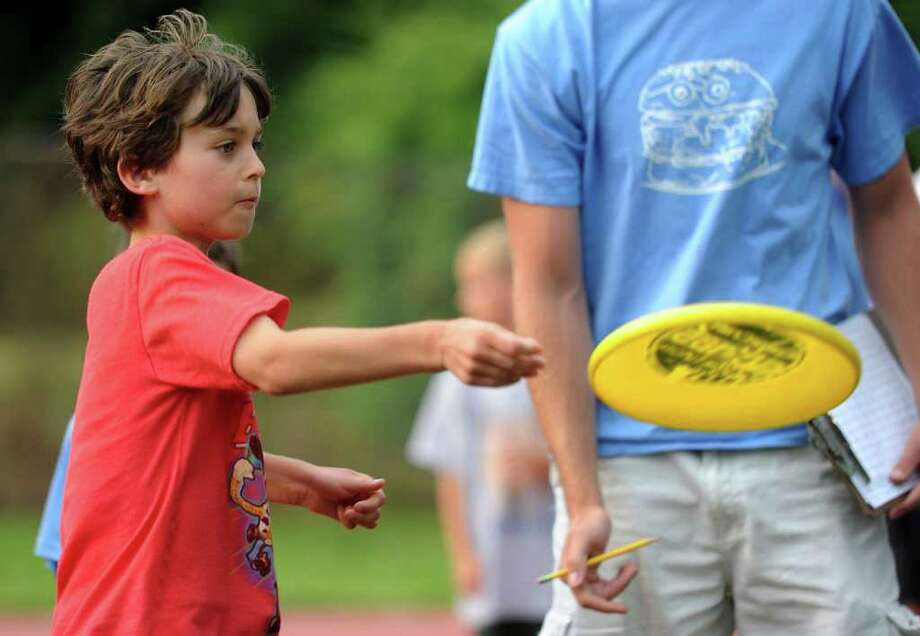 Jasper Cahn, 6, participates in the frisbee toss during Thursday's Westport Age Group Track Meet at Staples High School on July 7, 2011. Photo: Lindsay Niegelberg / Connecticut Post