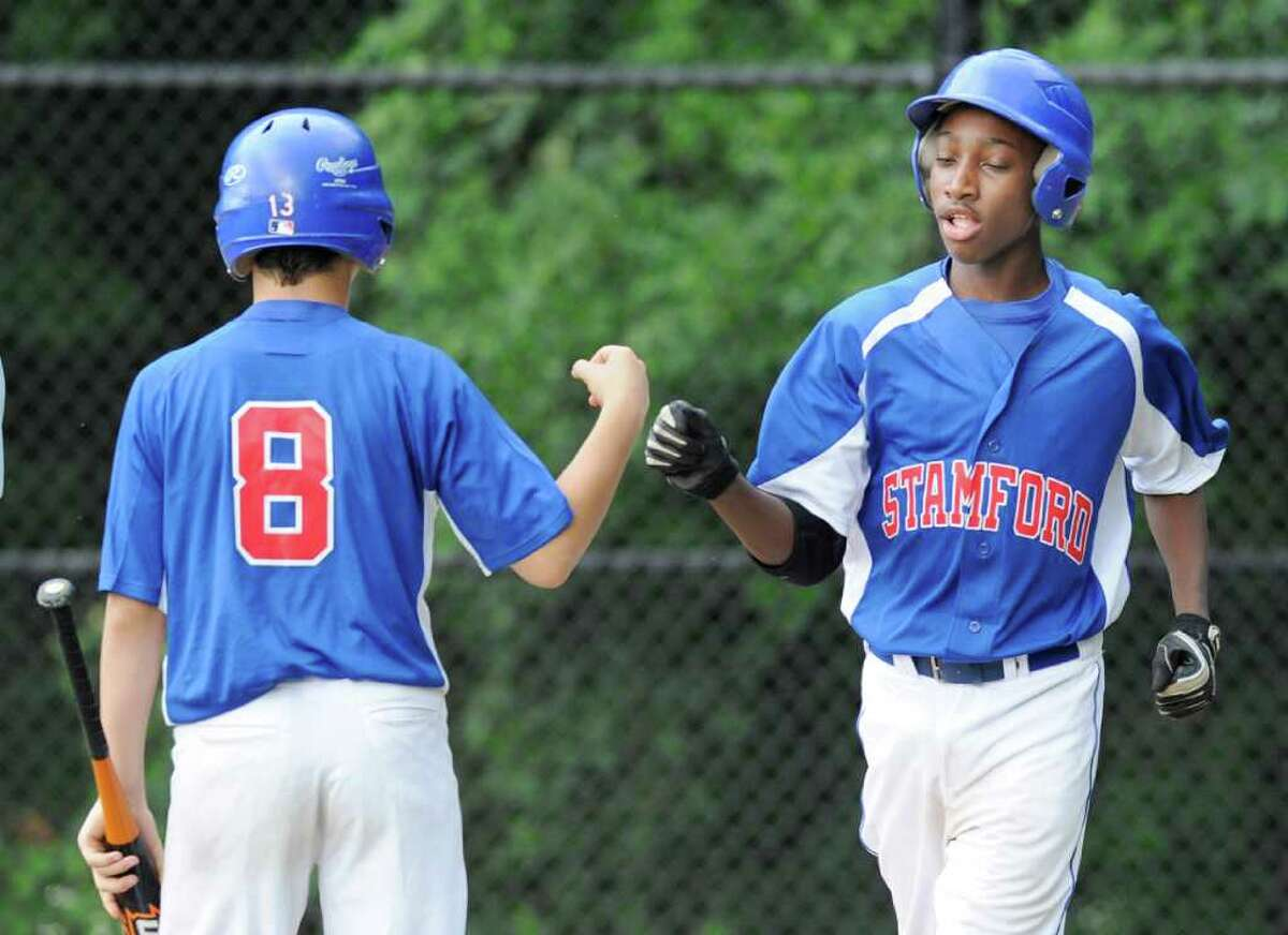 Dave Lature, right, of Stamford is congratulated by teammate Michael D'Amico # 8, left, after Lature scored during the top of the first inning in the Stamford vs. Greenwich U-13 Babe Ruth baseball tournament game at Darien High School Thursday night, July 7, 2011.