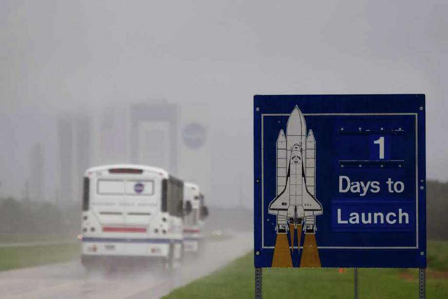 A sign counts down the days to launch as tour buses pass in a heavy downpour at the Kennedy Space Center in Florida on Thursday, July 7, 2011.  Thunderstorms on Thursday, and an unfavorable forecast for Friday,  threatened the scheduled final shuttle launch. ( Smiley N. Pool / Houston Chronicle ) Photo: Smiley N. Pool, Staff / © 2011  Houston Chronicle