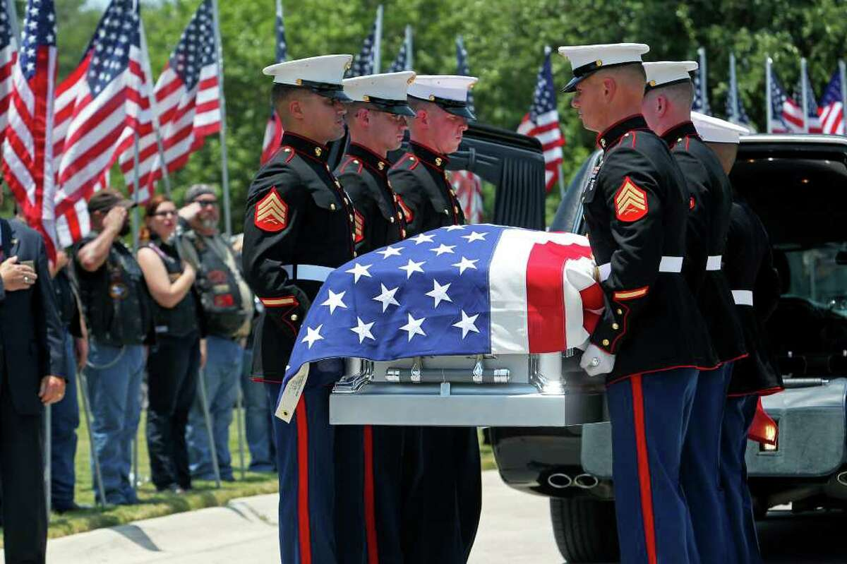 Marines unload the casket of Lance Cpl. John Farias at his Fort Sam Houston National Cemetery burial service on Thursday, July 7, 2011.