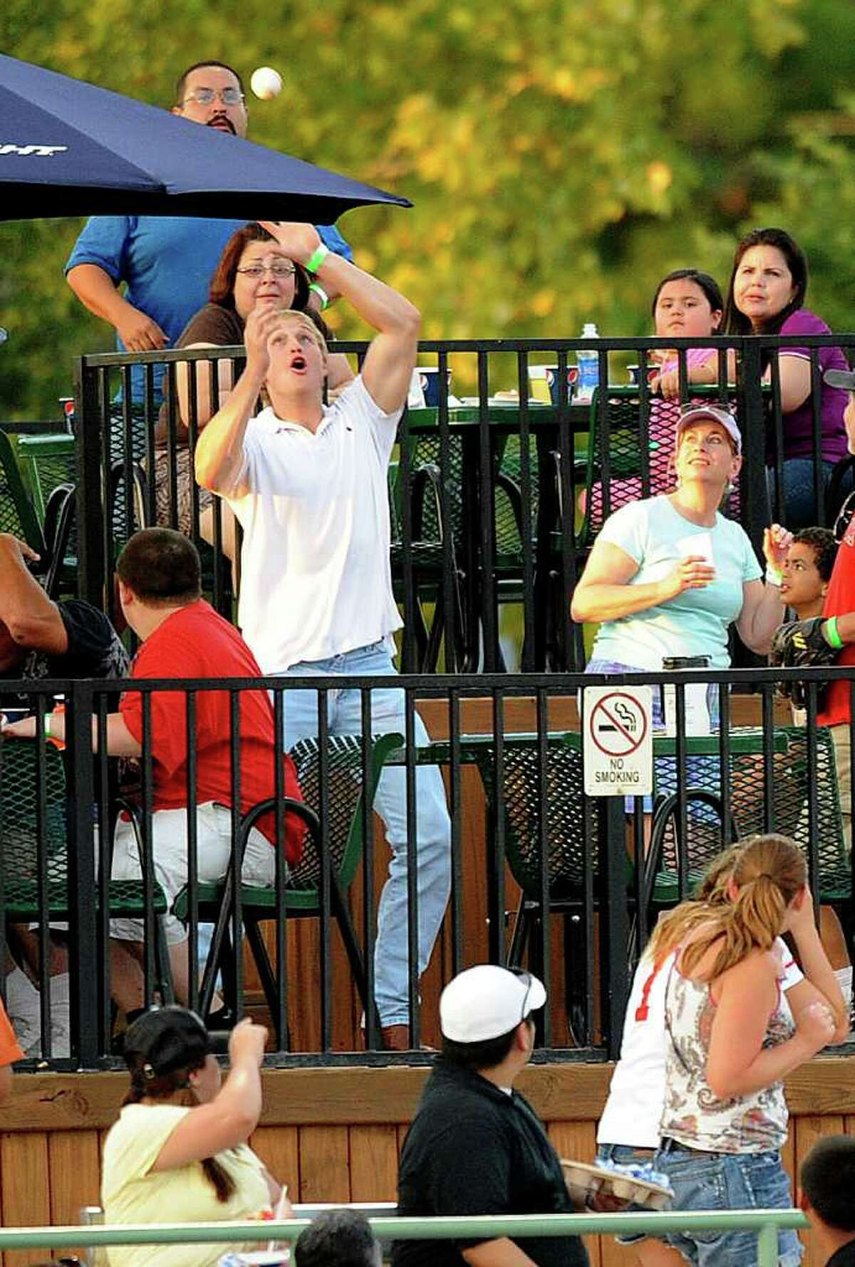 A fan reaches for a foul ball hit into the stands during Texas League action between the Northwest Arkansas Naturals and the San Antonio Missions at Wolff Stadium on Thursday, July 7, 2011. BILLY CALZADA / gcalzada@express-news.net
