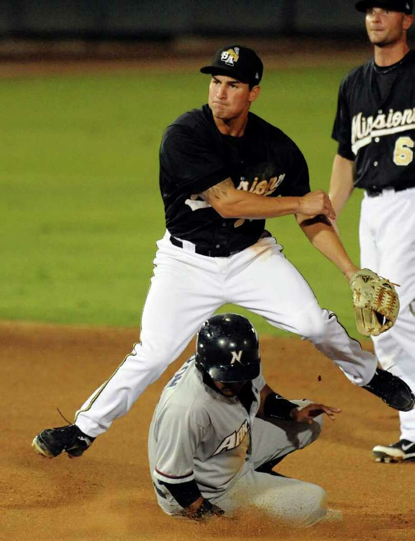 San Antonio Missions shortstop Dean Anna turns a double play as Christian Colon of the Northwest Arkansas Naturals slides in during Texas League action at Wolff Stadium on Thursday, July 7, 2011. BILLY CALZADA / gcalzada@express-news.net