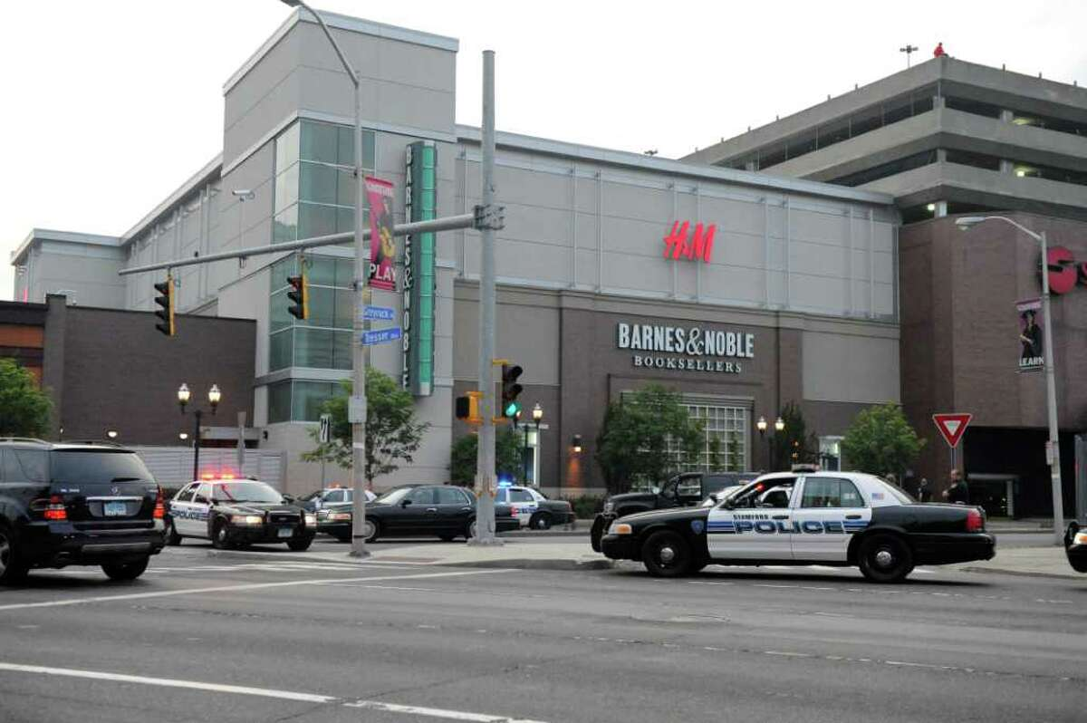 Police contain the scene as a man sits at the edge of the parking garage roof of the Stamford Town Center on Greyrock Place July 7, 2011.