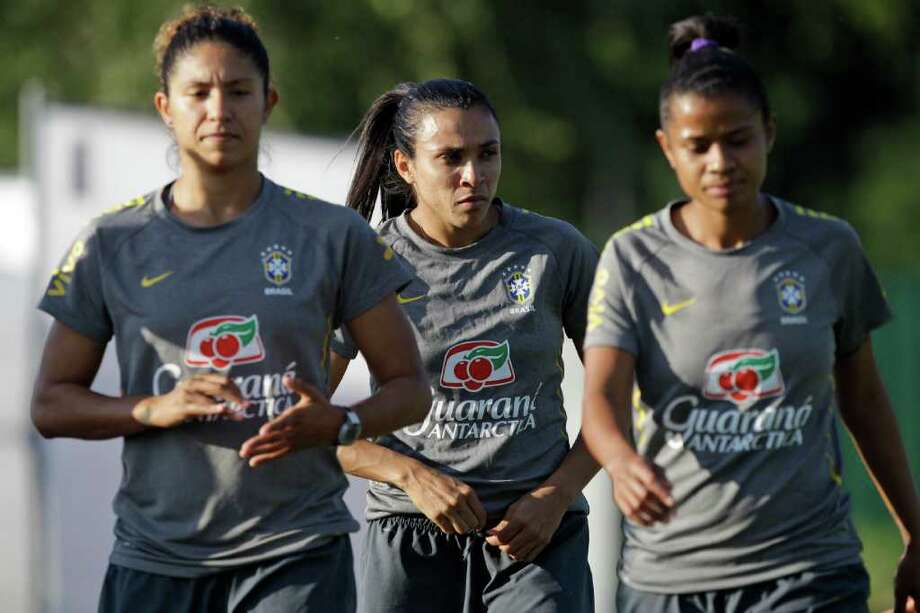 Brazil players, from left, Cristiane, Marta,  and Grazielle walk together during a training session in preparation for a quarterfinal match against the United States during the Women?s Soccer World Cup in Dresden, Germany, Friday, July 8, 2011. (AP Photo/Marcio Jose Sanchez) Photo: Marcio Jose Sanchez, STF / AP