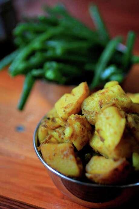 Amchur potatoes take their bright flavor from powder made from dried green mangos. Photo: Mayra Beltran, Staff / Houston Chronicle