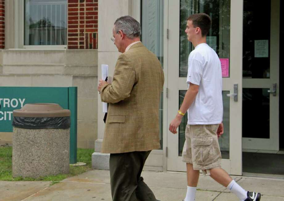 Patrick Chamberlain, 16, of Wynantskill, right, walks past the Troy City Court, accompanied by his attorney, Henry Bauer, left, after posting bail on Friday, July 8, 2011. Chamberlain is charged with two counts of felony gang assault. (Erin Colligan / Special To The Times Union)