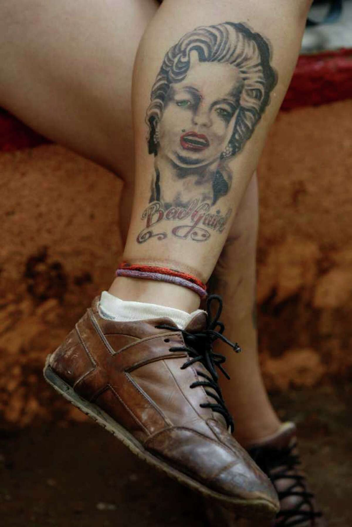 A tattoo depicting Marilyn Monroe is seen on a leg of a woman at the Atenas Rock Festival in Matanzas, Cuba, Saturday, June 18, 2011. From June 17 to June 19 Matanzas hosts the 10th National Atenas Rock Festival that gathers rock bands from across the country, during which a tattoo convention and music conferences are held. (AP Photo/Javier Galeano)