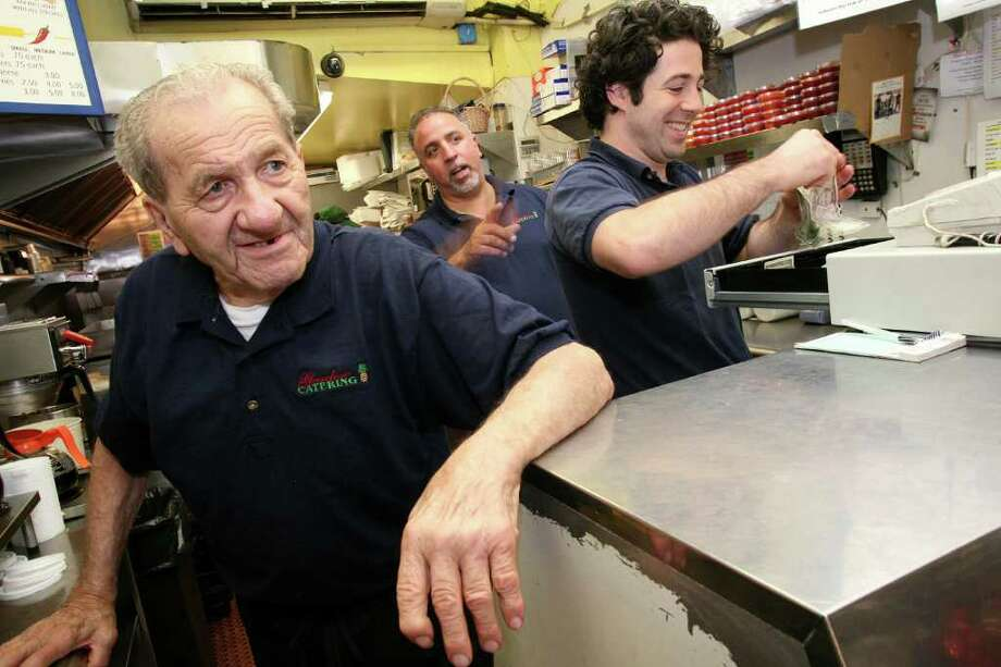 "Eighty-nine-year-old Garden Catering employee Frank ""Hotsy"" Bertino, left, keeps an eye out for customers along with Mike Paoletta, center, and Frank Carpenteri during the morning breakfast rush Friday, July 8, 2011. Photo: David Ames, David Ames/For Greenwich Time / Greenwich Time Freelance"