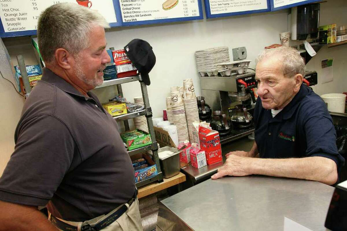 Frequent customer Bill Bennett, left, speaks with 89 year old Garden Catering employee Frank
