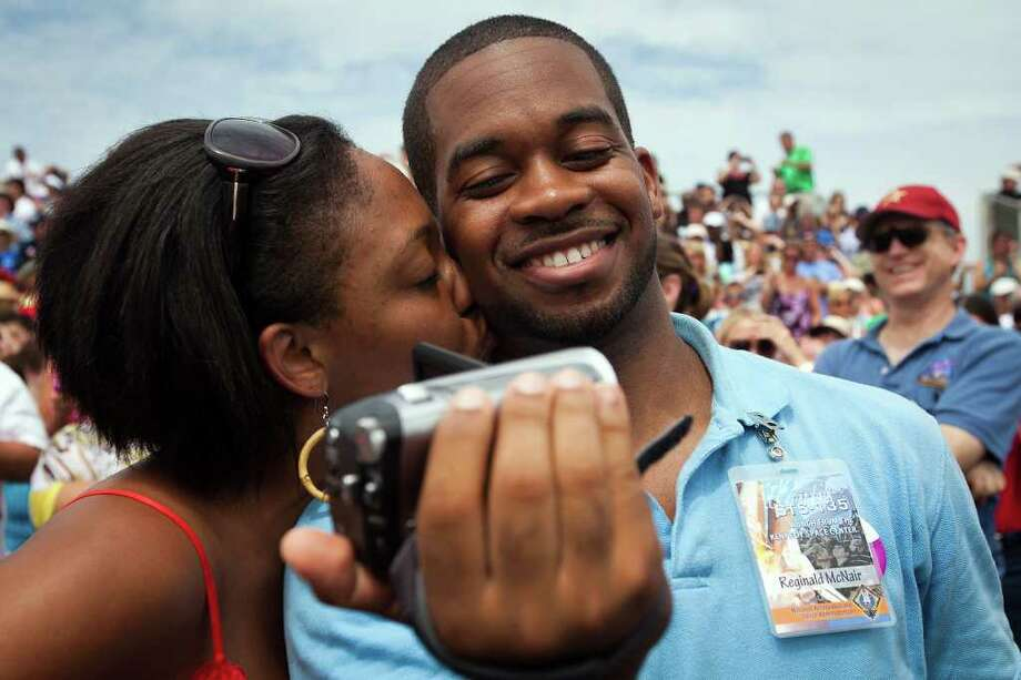 Reginald McNair, the son of NASA astronaut Ron McNair, who was killed in the Challenger accident in 1983, gets a kiss from his wive Shayla before watching the space shuttle Atlantis launches for the STS-135 mission to the International Space Station in the final mission of the space shuttle program at the Kennedy Space Center in Florida on Friday, July 8, 2011.  ( Smiley N. Pool / Houston Chronicle ) Photo: Smiley N. Pool, Staff / © 2011  Houston Chronicle