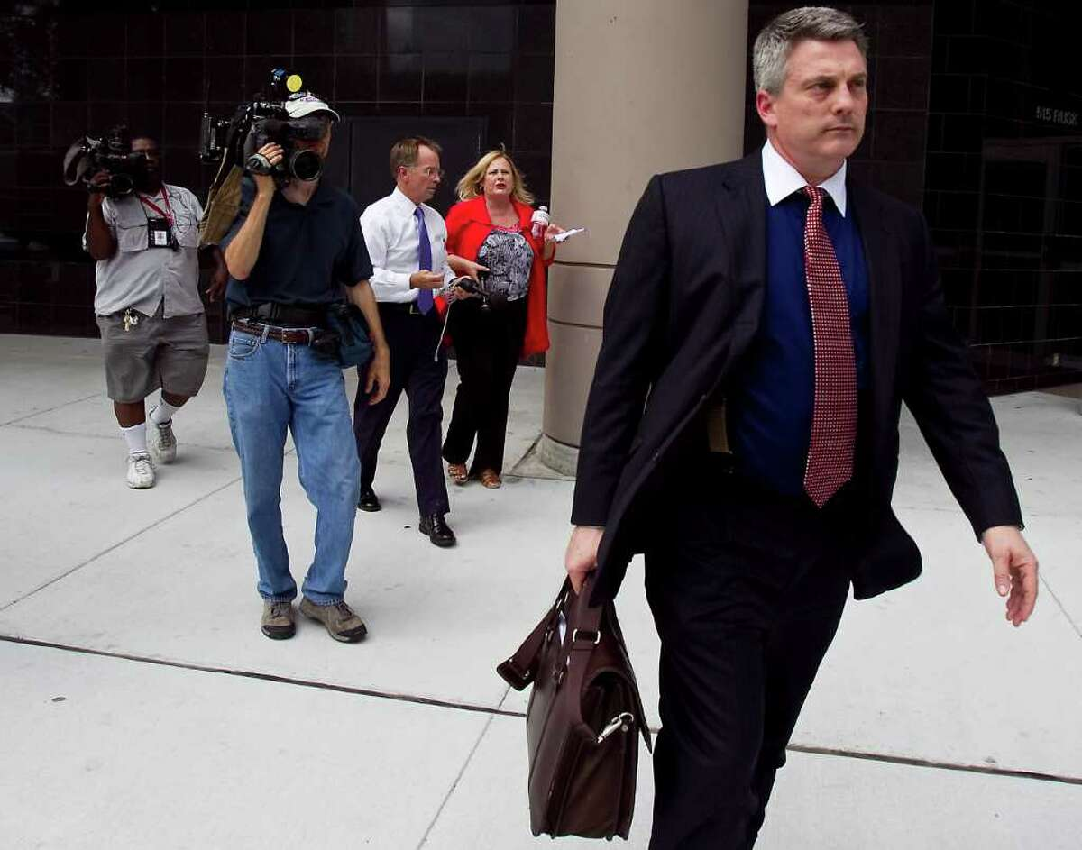 Todd Kelly, front, part of Jamie Leigh Jones' legal team, decideds to stop answering questions for local media and abruptly walks away after a jury rejected Jones' rape claim Friday, July 8, 2011, outside the Bob Casey Court House in Houston. Jones claims she was drugged and gang-raped while working for Kellogg Brown and Root in Iraq in 2005.n ( Nick de la Torre / Houston Chronicle )