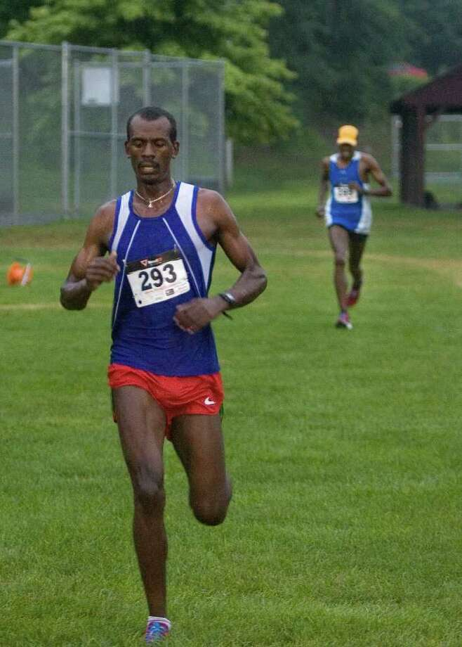 Kumsa Megersa, left, crosses the finish line in first place as fellow Bronx, NY, resident Abiyot Endale finishes in second place during the New Milford Moonlight Run 5K road race on Friday, July 8, 2011.  Both men are originally from Ethiopia. Photo: Jason Rearick